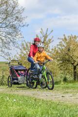 Mutter mit Kindern machen Radtour in aufblühender Natur