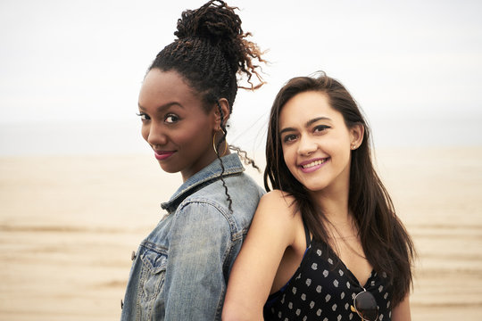 Smiling women back to back on beach