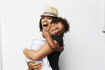 Smiling Mixed Race woman hugging daughter