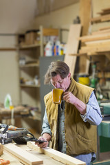 Caucasian carpenter drinking coffee and texting on cell phone in workshop