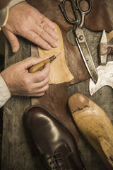 Hands of shoemaker using awl on leather