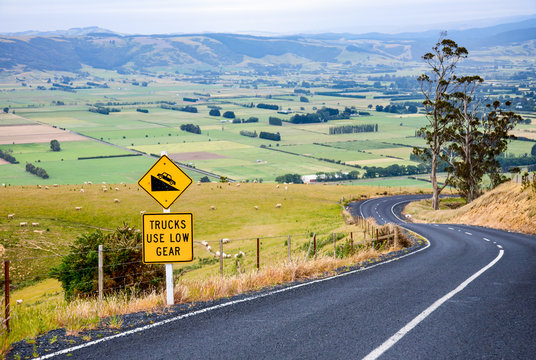 Curvy road with Steep Hill Descent warning road sign in New Zealand