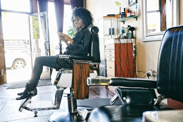 Smiling Black hairdresser texting on cell phone in hair salon