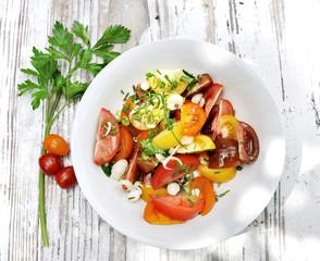 assiette de tomates accompagnées d'herbe sur table