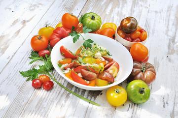 salade de tomates dans assiettes et différentes variétés de tomates entières