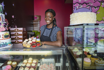 Black business owner showing cupcakes at bakery display case