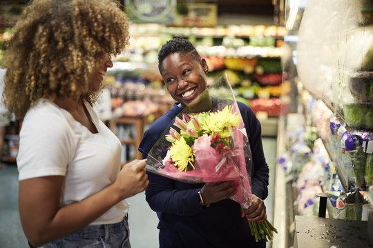 Black woman showing bouquet to girlfriend in store
