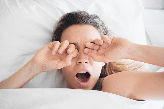 Donna sbadiglia a letto, sonno al mattino