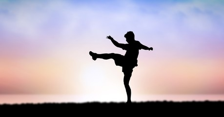 Silhouette of man exercising against sky during sunset