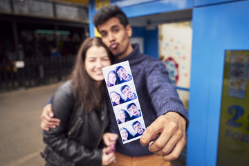 Couple showing photograph strip from photo booth