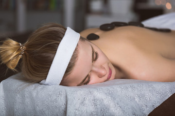 Young woman getting lastone therapy in spa