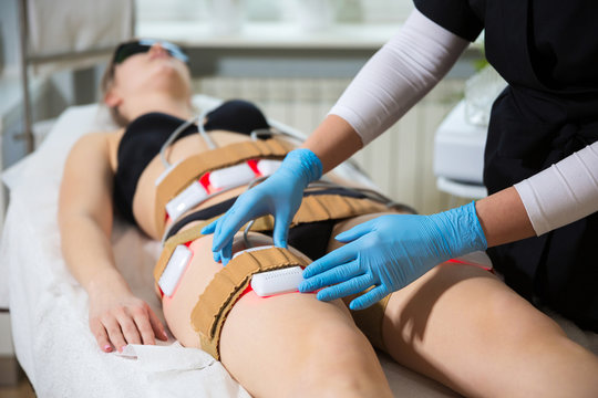 Woman receiving slimming lipo laser therapy in spa