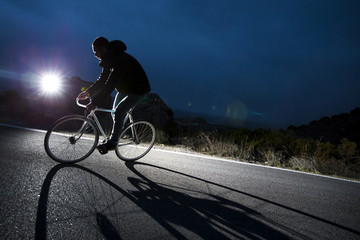 Cyclist man riding fixed gear sport bike in sunny day on a mountain road. Nocturne image.