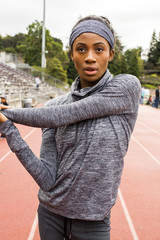 Serious Black athlete stretching arms on track