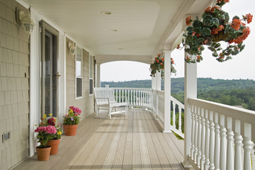 Large front porch of shingle style home with great view of tree tops