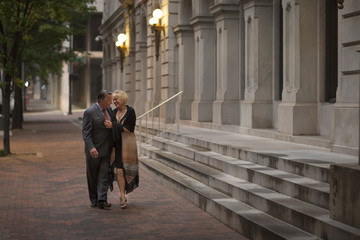 Older romantic couple walking on city sidewalk