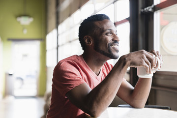 Smiling Black man sitting at window in coffee shop