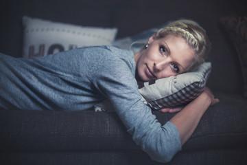 Blonde junge Frau liegt mit dem Kopf auf dem Kissen (Bauchlage, seitlich)