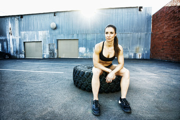Mixed Race woman sitting on heavy tire outdoors