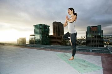 Caucasian woman doing yoga urban rooftop