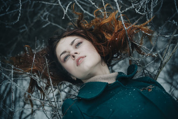Serious Caucasian woman laying on icy branches