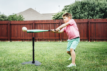 Boy playing with t-ball in backyard
