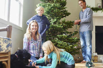 Caucasian family decorating Christmas tree