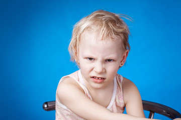 Angry child on a blue background
