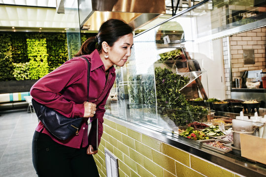 Curious Japanese businesswoman looking at salad in food court