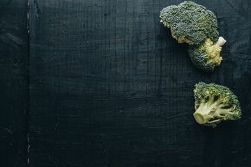 Space for text. Closeup of fresh green Broccoli over black wooden background. Top view