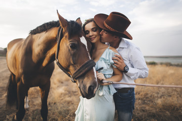 Caucasian cowboy kissing woman on cheek near horse