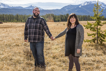 Smiling Caucasian couple holding hands in field