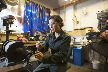 Mixed Race woman holding metal rod in workshop