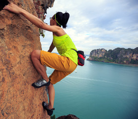 Foto op Aluminium Alpinisme young woman rock climber climbing at seaside cliff