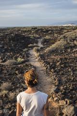 Caucasian woman standing on trail through rocks