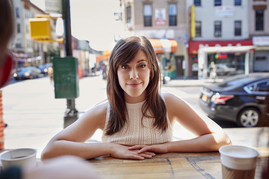Smiling Caucasian woman leaning on counter in city