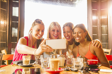 Woman posing for cell phone selfie in restaurant