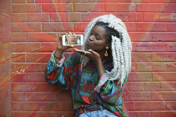 Woman leaning on brick wall showing photograph of lips
