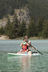 Caucasian mother and son sitting on paddleboard on lake