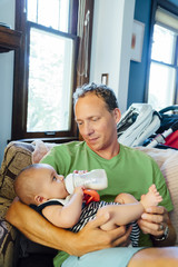Father holding baby son drinking milk from bottle