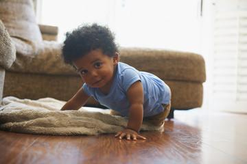 Black baby boy crawling on blanket