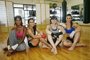 Smiling women sitting on floor of gymnasium