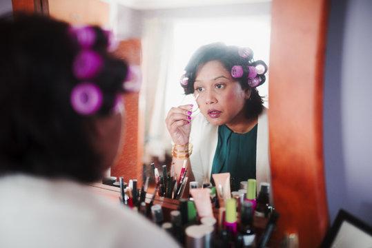 Indian woman wearing curlers applying makeup