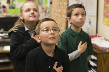 Caucasian students standing for Pledge of Allegiance