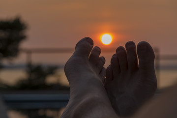 Setting summer sun viewed through bare feet outside by the pool