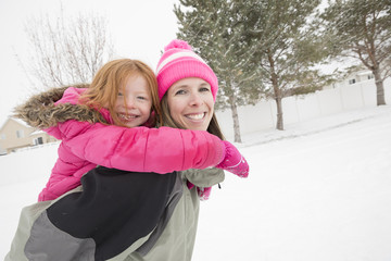 Smiling mother carrying daughter piggyback in winter