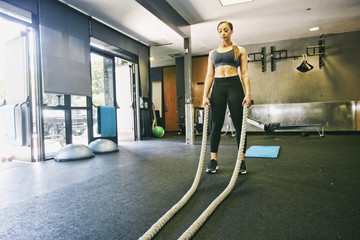 Mixed Race woman working out with heavy ropes in gymnasium