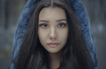 Portrait of serious Mixed Race teenage girl wearing blue hood
