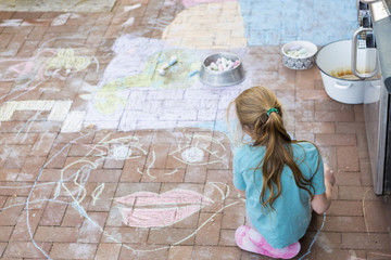 Caucasian girl drawing face with chalk on patio bricks