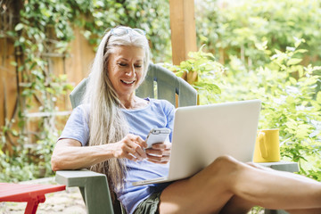 Caucasian woman cell phone and laptop on backyard patio